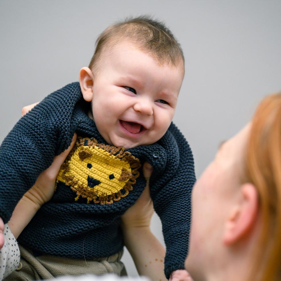 Mutter mit lachendem Neugeborenem Baby