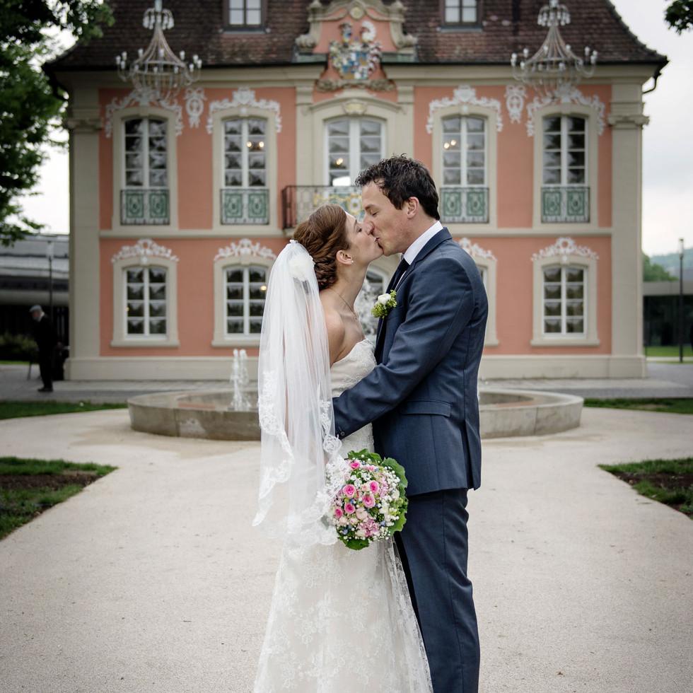 Brautpaar küsst sich vor Schloss
