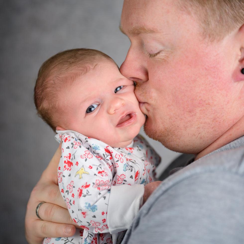 Vater küsst Neugeborenes Baby