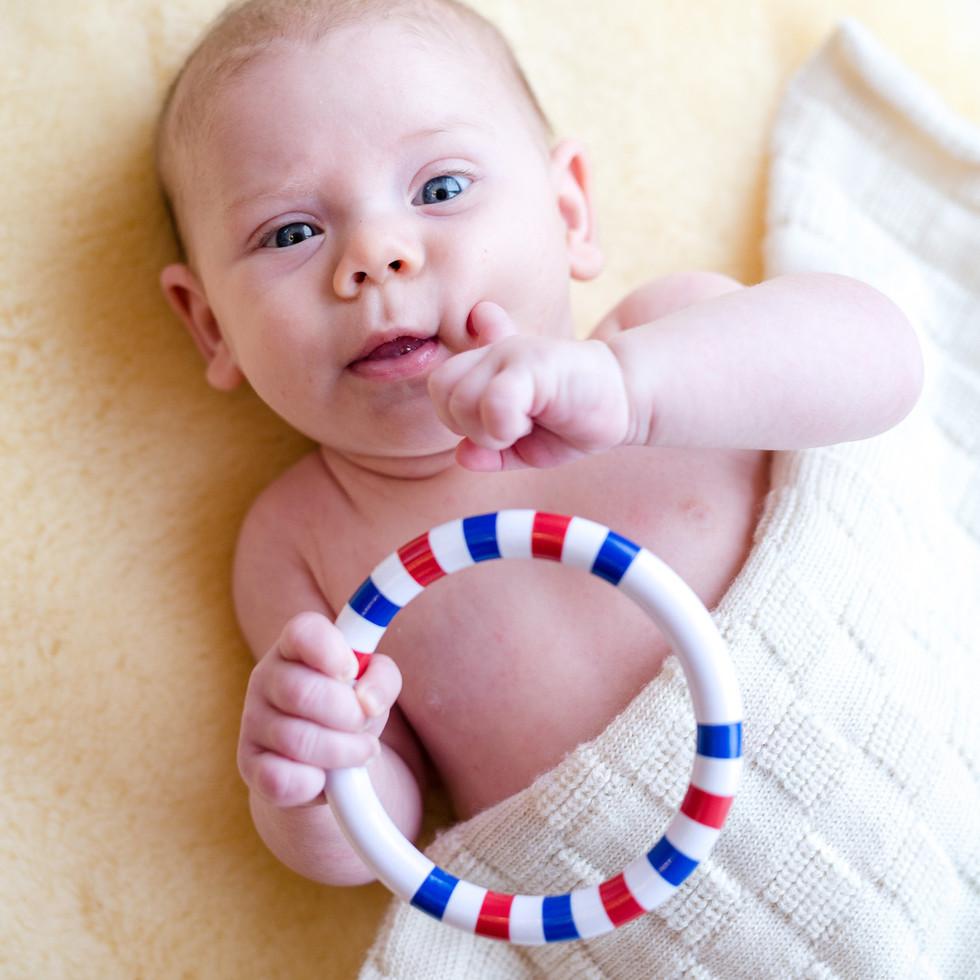 Neugeborenes Baby mit Rassel