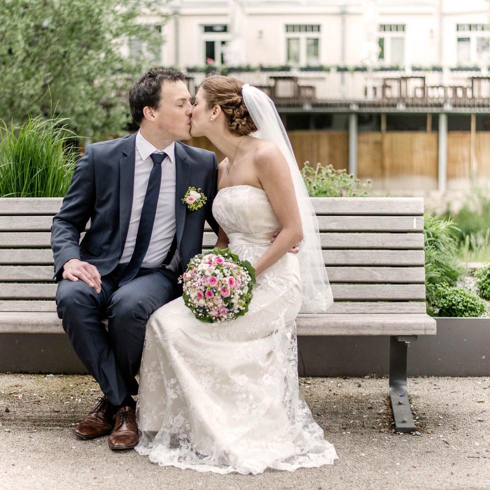 Brautpaar küsst sich auf Bank