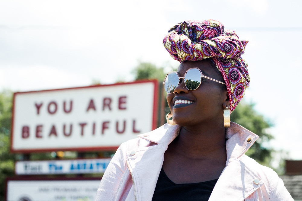 Woman of colour standing in front of you are beautiful sign