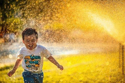 Boy playing underneath water sprinklers