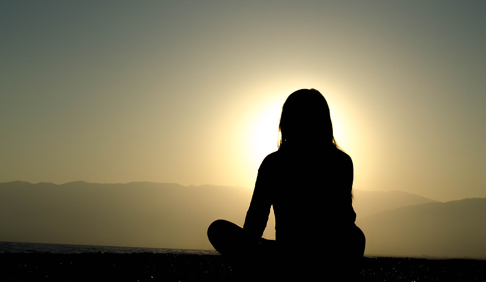 Silhouette of sitting women looking at sunset