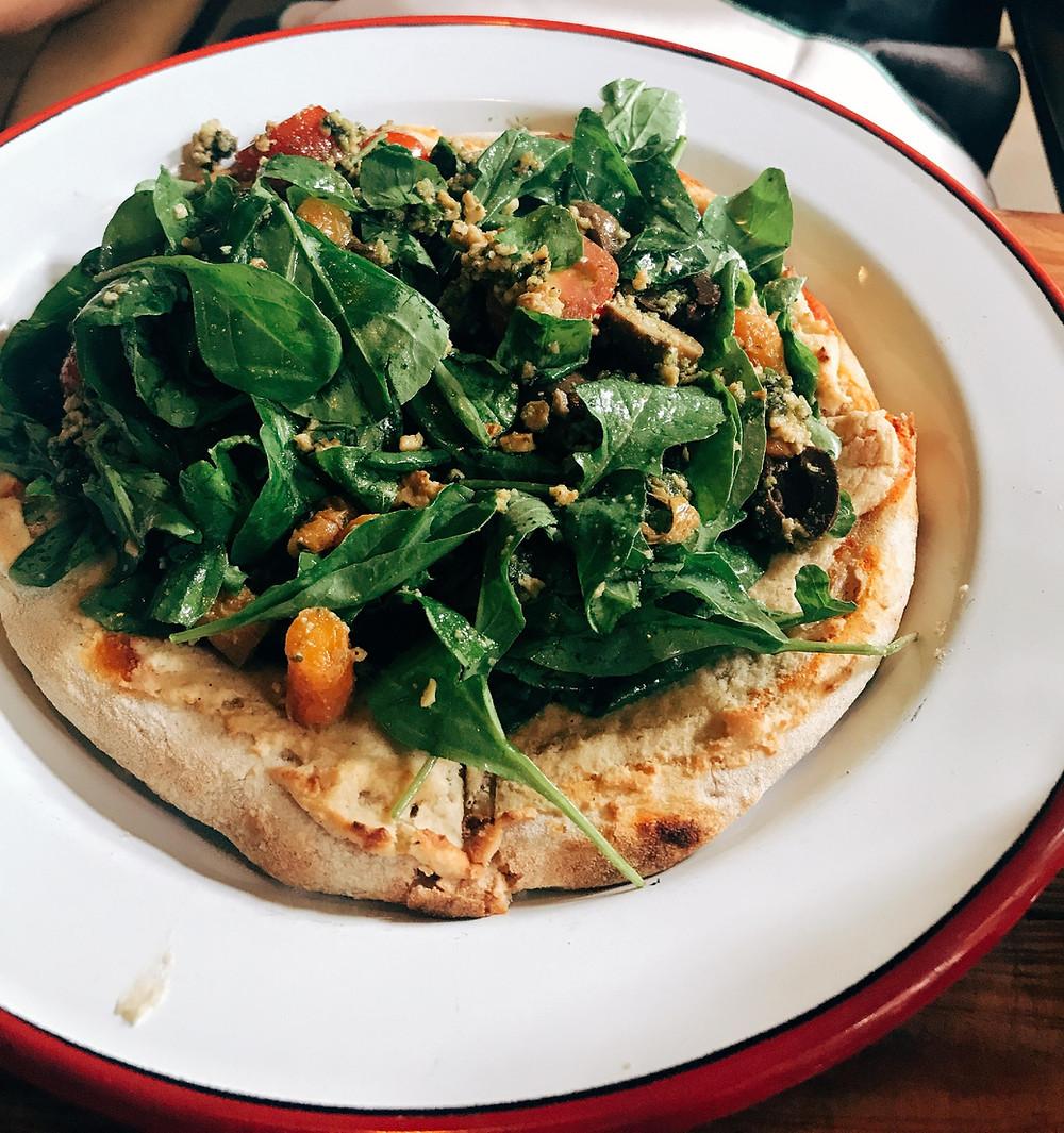Quinoa Pizza Veggie: pizza com massa de quinoa, com rúcula fresca, cenouras babys, queijo feta, azeitonas orgânicas, tomate cereja e pesto de kale e menta.