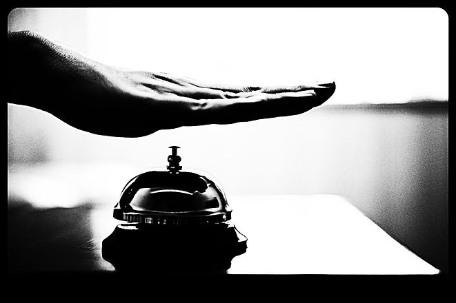 Hand ringing in service bell on wooden t
