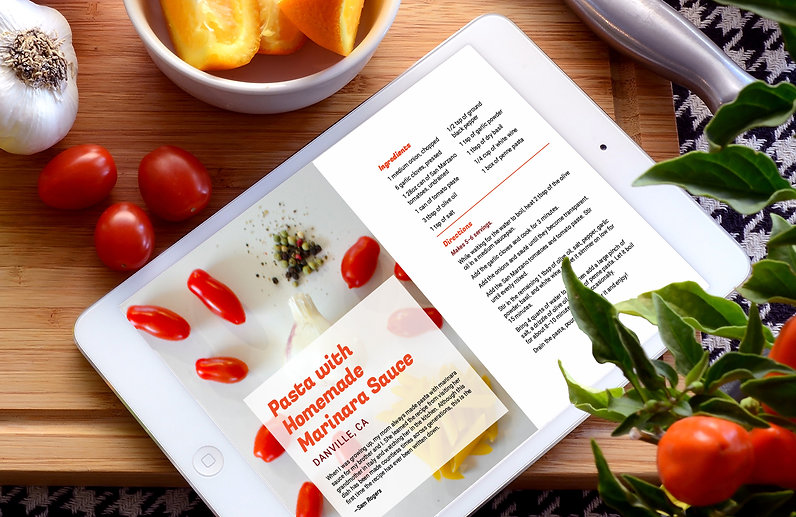A tablet showing a cookbook page sits on a cuttingboard next to a knife and ingredients.