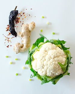 Dried chilis, ginger root, green onion, and cauliflower on a white bakground.
