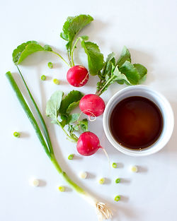 Radishes, green onions, and soy sauce on a white background.