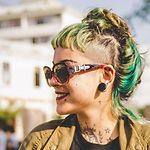 A smiling woman with green and blond hair and sunglasses.