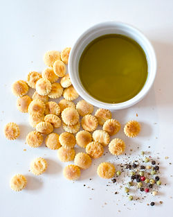 Oyster crackers, cooking oil, and rainbow pepper on a white background.