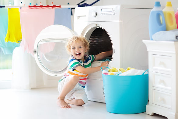 Child in laundry room with washing machi