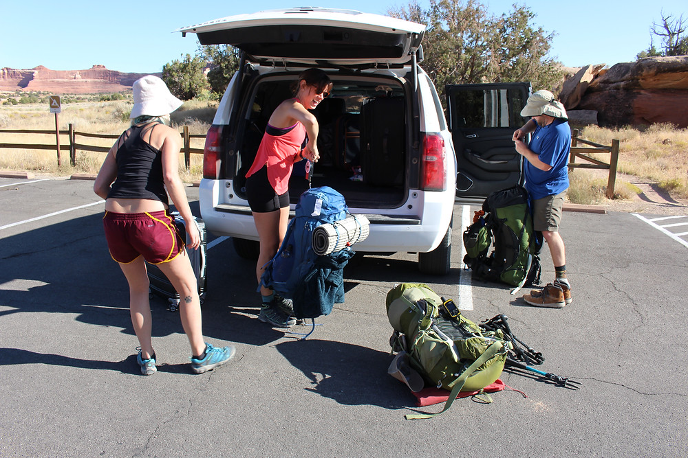 Three people pack bags from a truck, getting ready to backpack