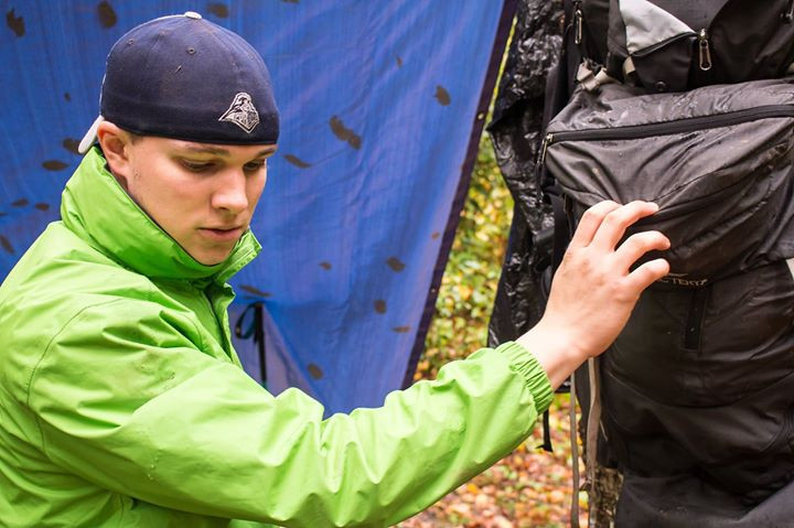 Mark packs up his gear that has stayed relatively dry under a tarp
