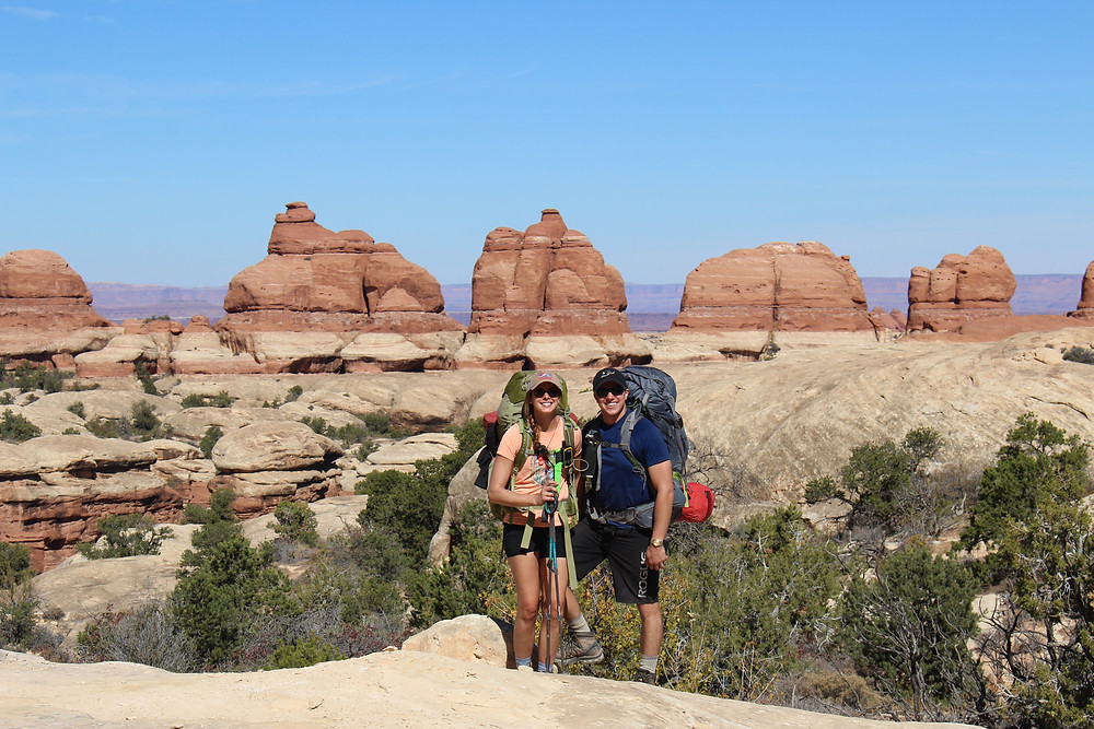 Two backpackers pose for a picture in front of desert rock formations.