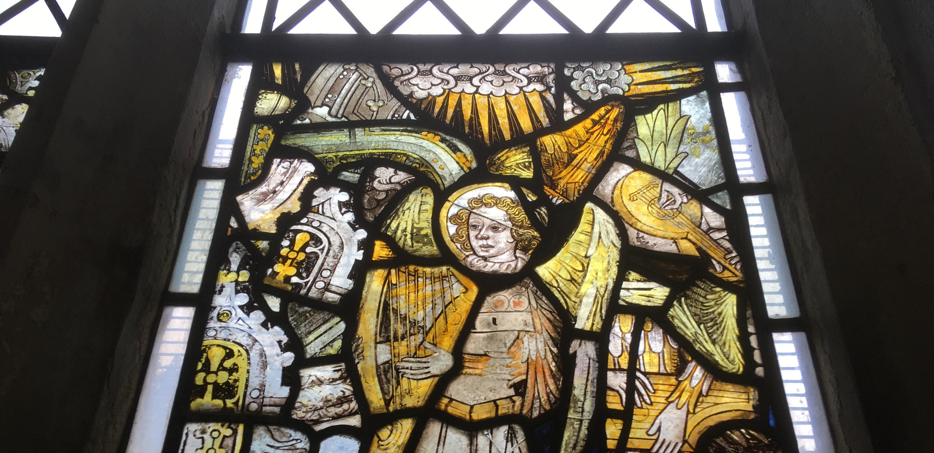 A harp player from the Cawston window, with random bits of lute player and psaltery player too. The chunky bits on the soundbox of the harp are suggestive of brays, which would fit the fifteenth-century date.