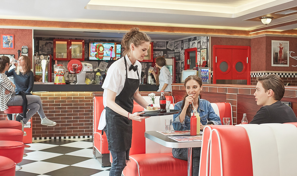 waitress serving two people in a diner