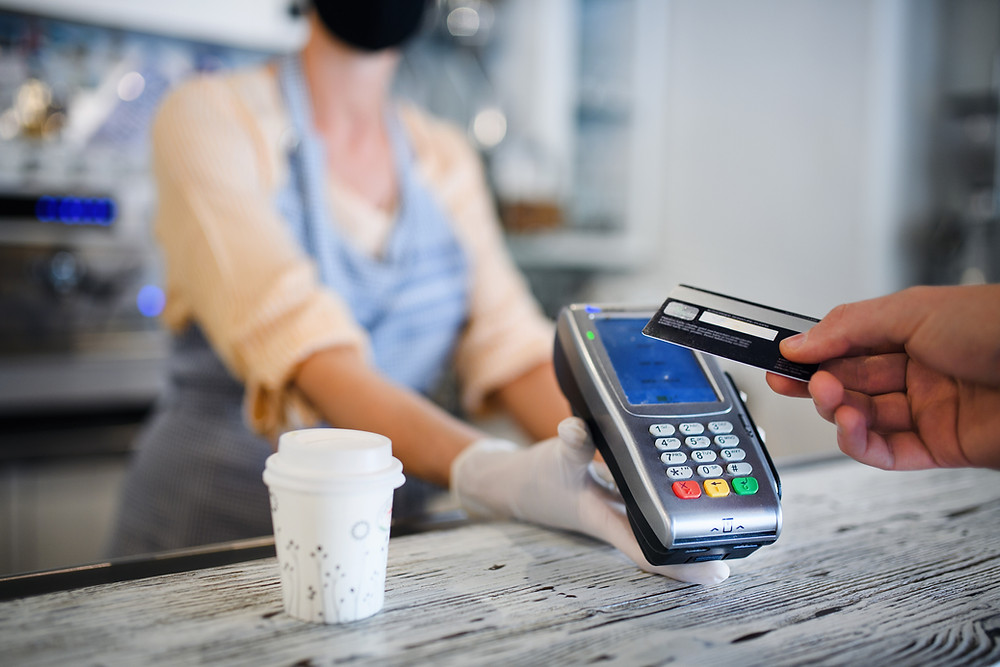 Customer paying for coffee by tapping their credit card