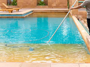 113054146-worker-cleaning-swimming-pool-