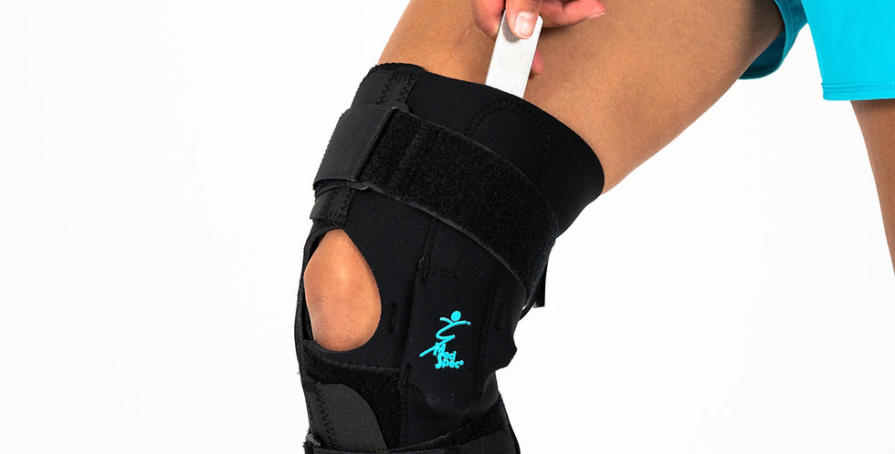 A woman wearing the Med Spec Gripper knee brace is pulling out one of the metal hinges used to provide ligament support
