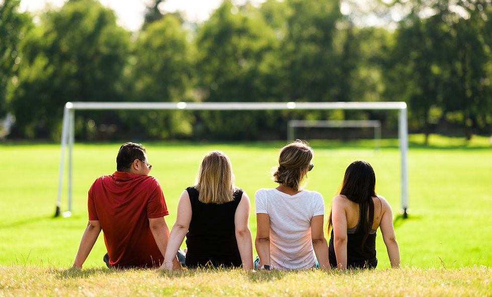 Four friends including a man and three young women sitting shoulder to shoulder on the grass at a soccer field laughing in the summer sun.