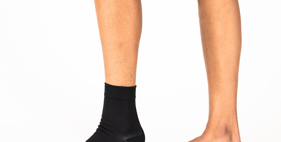 Side view of a women's leg and ankle wearing a black Bort ankle compression sleeve for either a mild ankle sprain or swelling