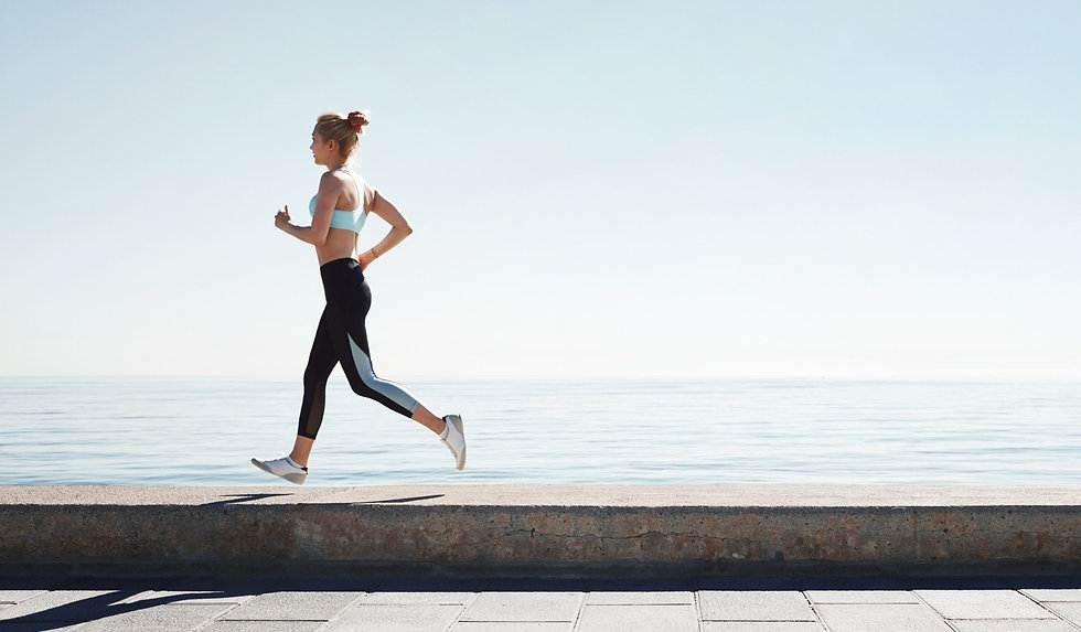 Woman running ocean side with knee pain