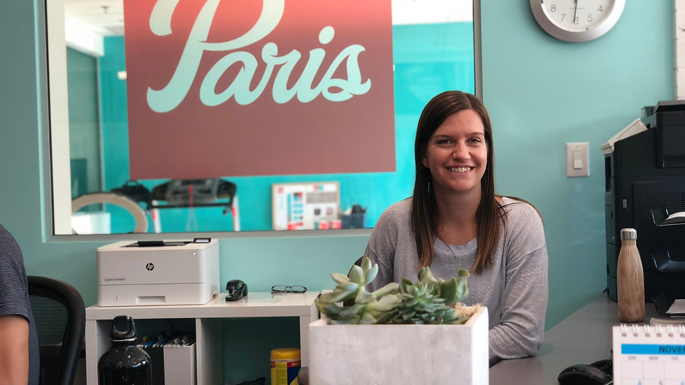 A smiling female employee sitting at the reception desk of the Paris everyBODY location at 1861 W Broadway in Vancouver, BC