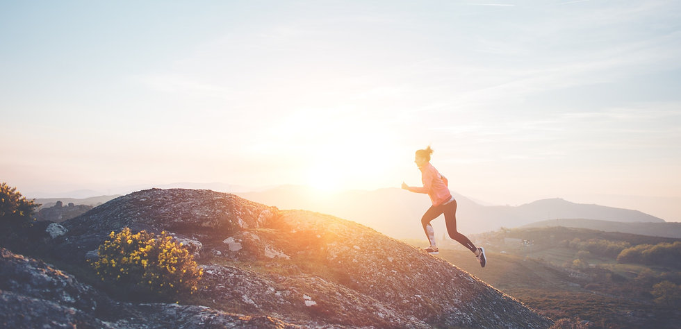 Aspirational woman wearing orthotics in her running shoes running to the top of a large hill at sunset