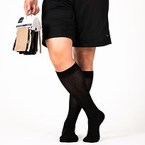 A pair of mens legs wearing Sigvaris Sea Island Cotton Everyday Compression socks to prevent leg swelling and fatigue.