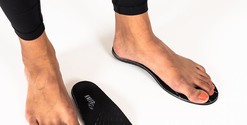 A pair of feet near a pair of off-the-shelf Kneed insoles in the Kneed2Run version that provide arch support in athletic shoe