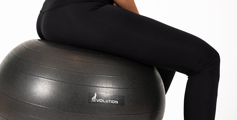 A woman sitting on the Evolution Chair that has a base on wheels and an exercise ball for improved posture