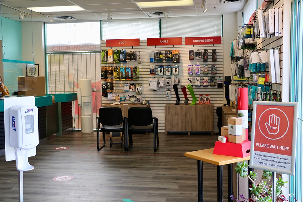 An interior shot of the Paris everyBODY Port Coquitlam location showcasing the front desk and a variety of ankle braces, insoles and compression socks.