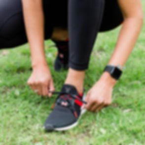 A woman in athletic clothing is bent down to tie up the laces of her running shoe with heel cups inside