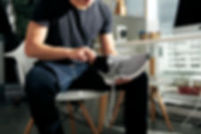A man sitting on a white chair is inserting a custom foot orthotic that he had made at Paris everyBODY into his grey sneaker