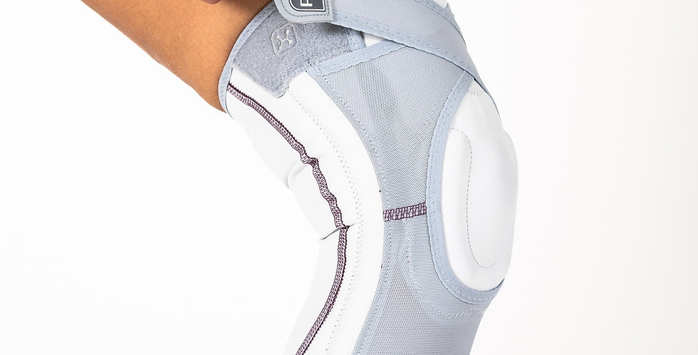 Side view of a woman closing the thigh strap of a grey Push Med Care Knee brace for patellofemoral pain syndrome