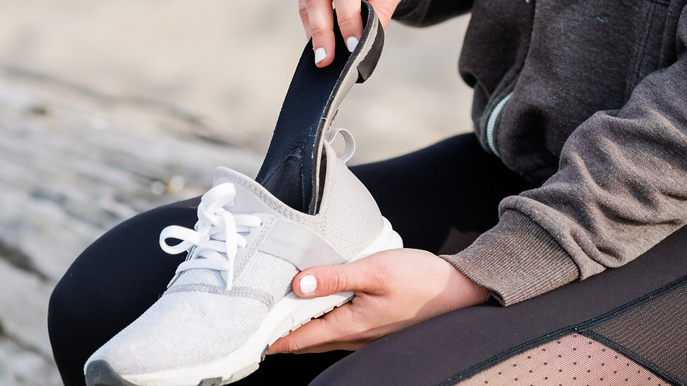 Close up of woman on a bench putting a sport custom foot orthotic into a pair of running shoes