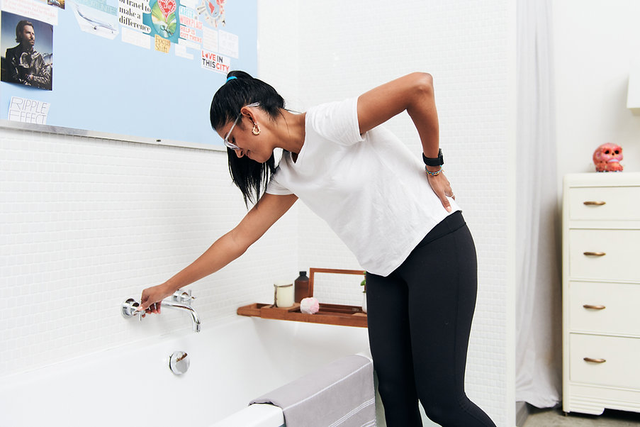 A young woman reaching over a bathtub to turn the faucet on with one hand and the other hand on her sore back.