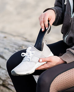 A woman in black workout clothes sitting on a bench at Jericho beach in Vancouver inserting sport orthotics into her white running shoe