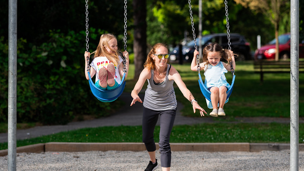 A mother joyfully pushing her two daughters on swings in the park during summer.