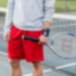 Man in grey sweatshirt and red shorts is holding a tennis racket on a tennis court while wearing a Push sports wrist support wrap
