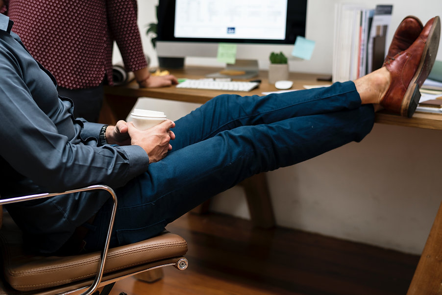 Man holding coffee with sore legs and feet on desk finding relief from swollen ankles