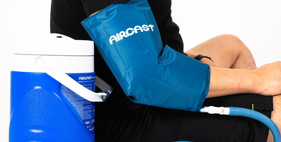 Side shot of a man wearing the elbow cryotherapy cuff attached to the Aircast cooler unit