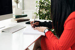 A woman wearing a red dress writing at a desk while wearing a Med Spec Tripod wrist splint to prevent carpal tunnel syndrome
