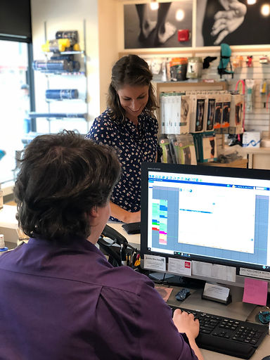 A female client purchasing resistance bands and posture support from Paris everyBODY + SportMed in Langley