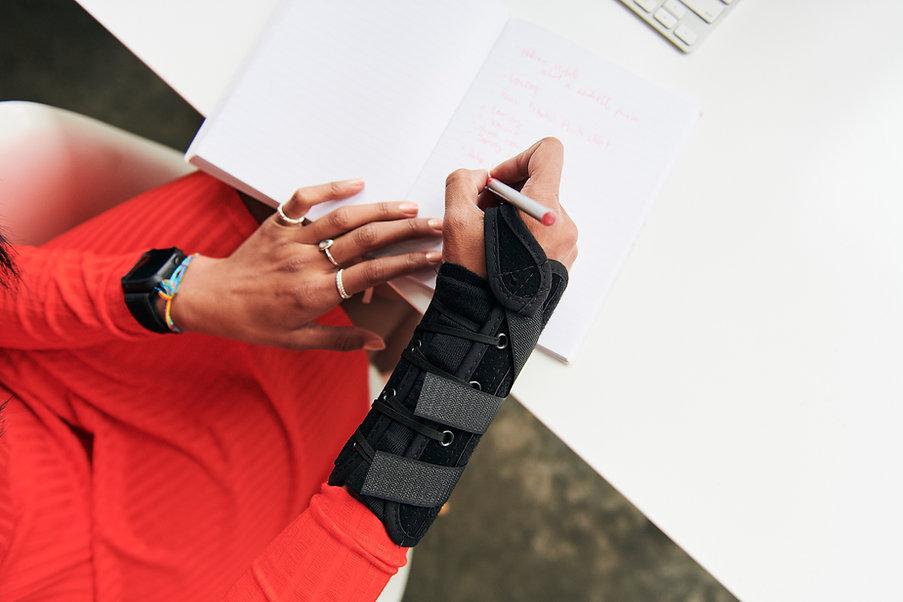 Woman wear a wrist brace writing on a desk