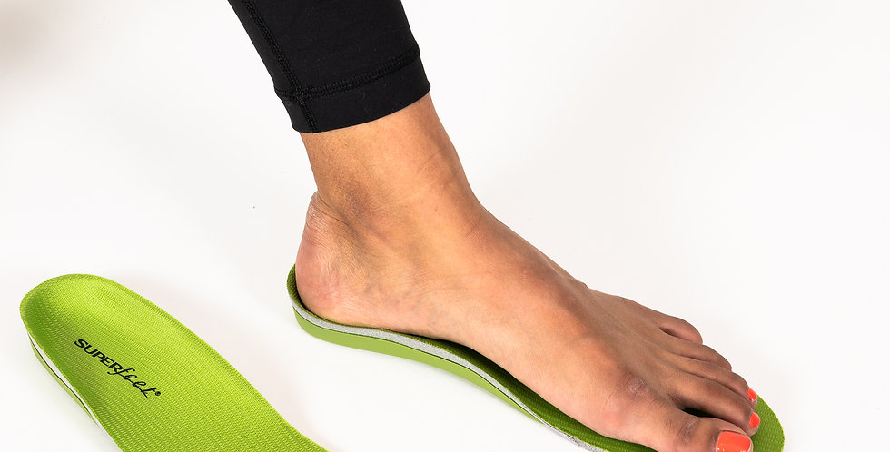 A foot resting on top of a pair of green Superfeet off-the-shelf insoles for athletic activity