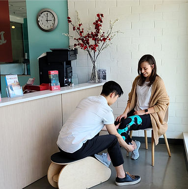 A Paris everyBODY staff member fitting a female client with a teal custom knee brace at 1861 W Broadway location in Vancouver