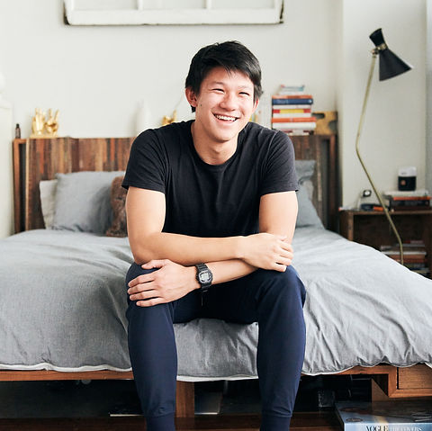 A smiling man recovered from plantar fasciitis is sitting on the edge of his bed