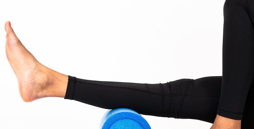A woman's calf on top of a blue foam roller to massage her calf